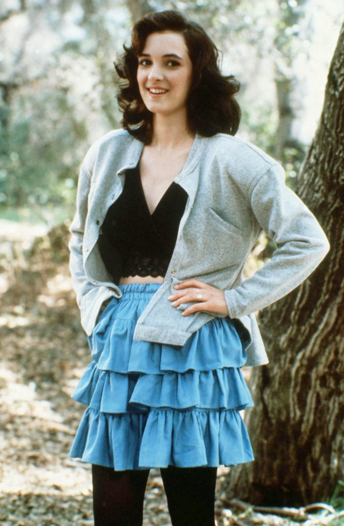 rara skirt in blue, worn with a black crop top, and a pale grey cardigan, by a young winnona ryder, 80's fashion pictures, smiling with hands on her hips