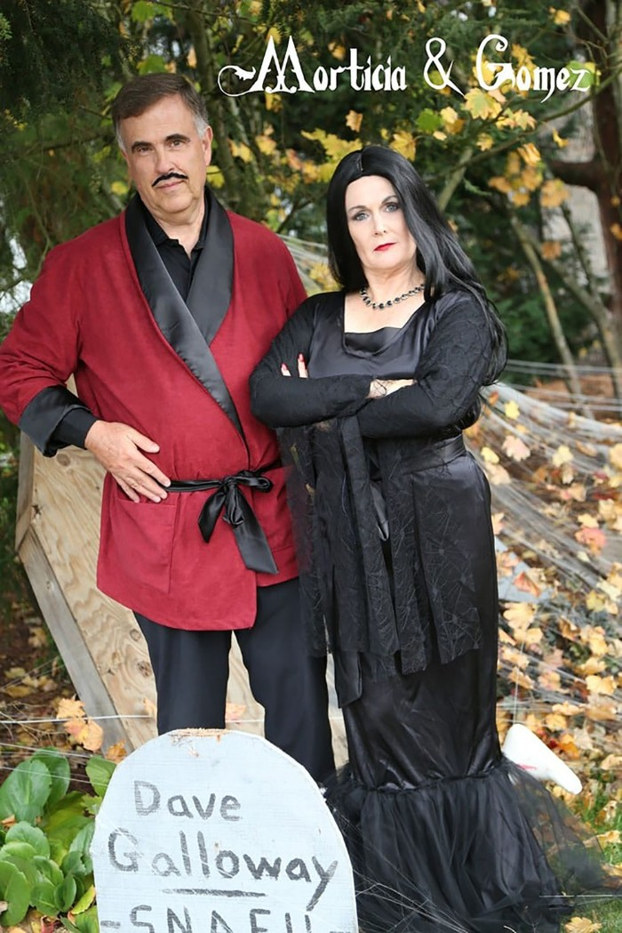 gomez and morticia addams, duo halloween costumes, worn by elderly man and woman, black and red bathrobe and faux mustache, black maxi dress and wig