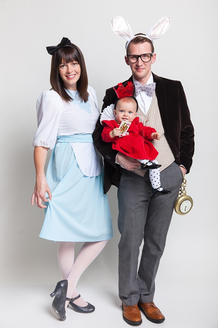 parents and a small baby, dressed like characters from alice in wonderland, the mother is alice, the father is the white rabbit, and the baby is the queen of hearts