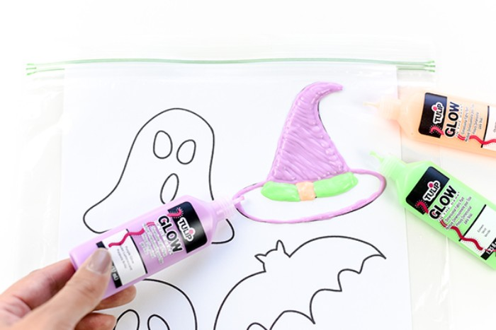 painting over a clear ziplog bag, containing a white sheet of paper, with simple halloween shapes, using a tub of purple paint, halloween party decoration ideas, glow-in-the-dark-stickers