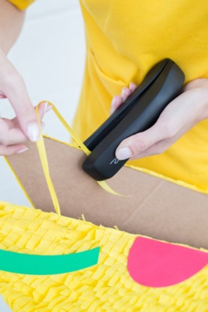 stapling a piece of yellow ribbon, on two decorated pieces of cardboard, using a black stapler, couples halloween costume ideas