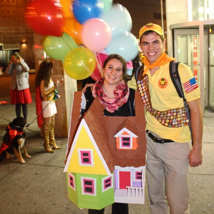 pixar's up inspired costumes, man dressed like a guilde, and a woman in a carboard house costume, decorated with many, multicolored balloons