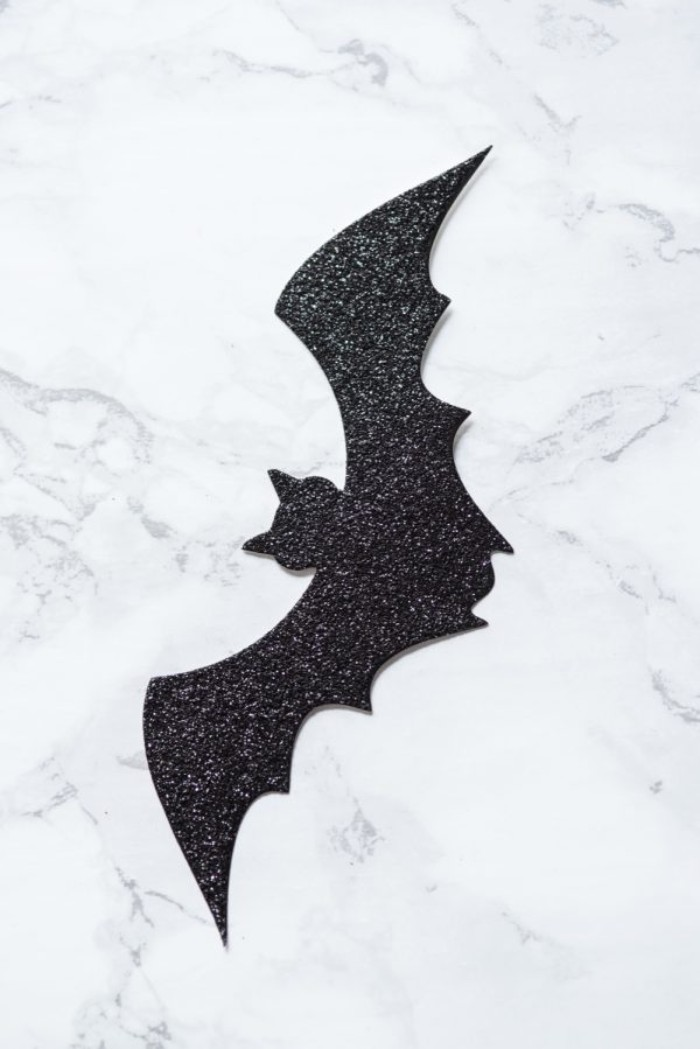 extreme close up, of a small bat shape, cut out from black glittering card, and placed on a marble surface