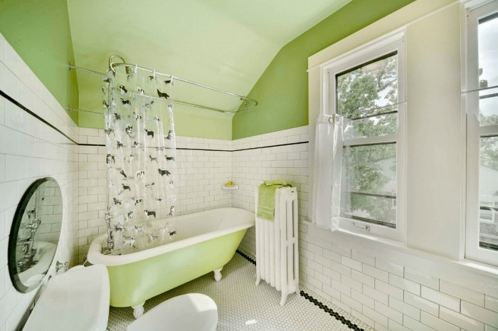subway tiles in white, with a black detail, covering the bigger part, of three pale green walls, bathroom color schemes, retro-style bathtub, two windows and a green ceiling