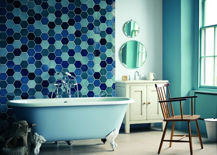 tiles in different shades of blue, with a beehive-like pattern, decorating the wall of a pale blue room, bathroom paint colors, vintage-style clawfoot bath