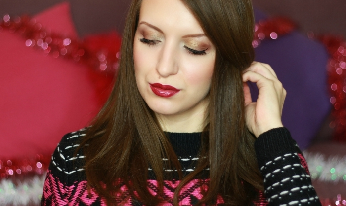 festive sweater in black, white and pink, worn by a pale brunette woman, with dark red glossy lipstick, and christmas eyeshadow in shimmering beige