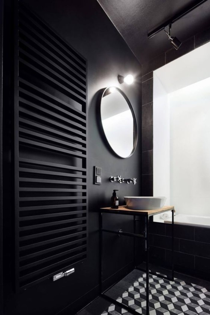 lightbulb glowing over a round mirror, mounted on a black wall, near a tall black towel rack, white grey and black tiled floor, white bath area