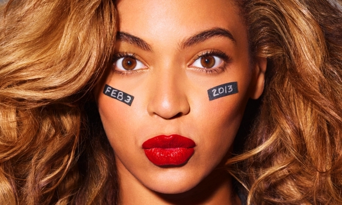 pouting expression made by beyonce, with caramel brown hair, red lipstick and black strips with white letters and numbers, on her cheeks