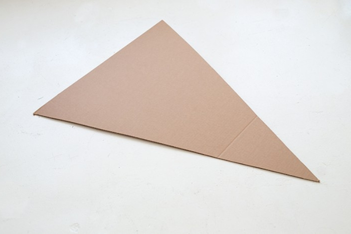triangular piece of beige cardboard, for making a pizza costume, couples halloween costumes, placed on a pale grey surface