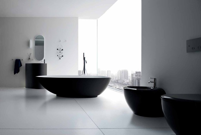 monochrome bathroom with white walls, black bathtub and sink, toilet and bidet, and two large windows