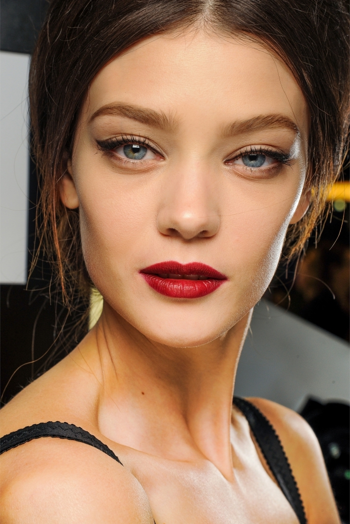 slim brunette female model, with blue eyes, wearing red lipstick, black mascara and eyeliner, holiday makeup 2017, in a black strappy top