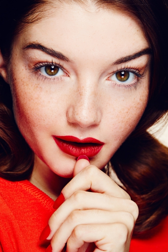 freckled brown-eyed young woman, with brunette hair, wearing a bright red top, red nail polish, and matching red lipstick