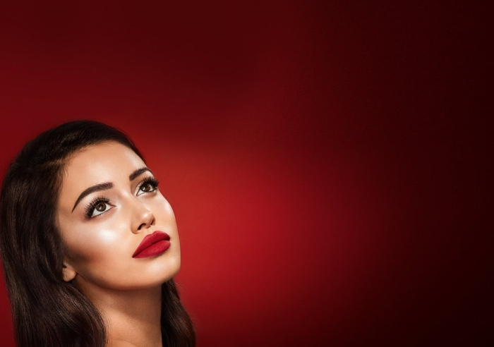 full lips with red lipstick, on a young brunette woman, with long dark hair, fake lashes and black mascara, christmas makeup, on a dark red background