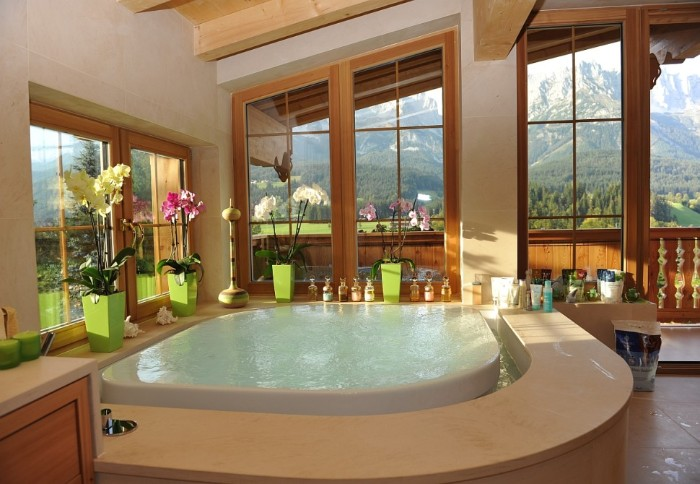master bath remodel, rustic cabin like house, containing a white hot tub, surrounded by several orchids, in light green pots, windows with mountain view