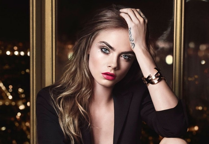 smokey eye shadow, and glossy red lipstick, worn by cara delevigne, eye makeup for red lips, brunette wavy hair, and a black blazer