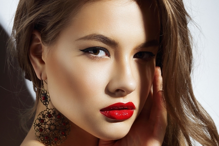 glossy red lipstick, and subtle black eyeliner, christmas makeup ideas, worn by a young brunette woman, with large ornamental earrings, and subtle blush