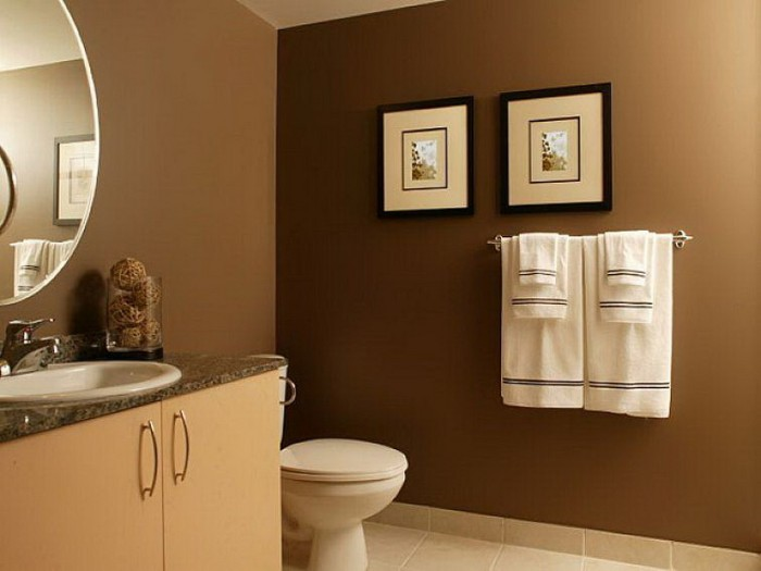 small bathroom paint colors, chocolate brown walls, decorated with a round mirror, and two framed artworks, pale beige cupboard, with an inbuilt sink