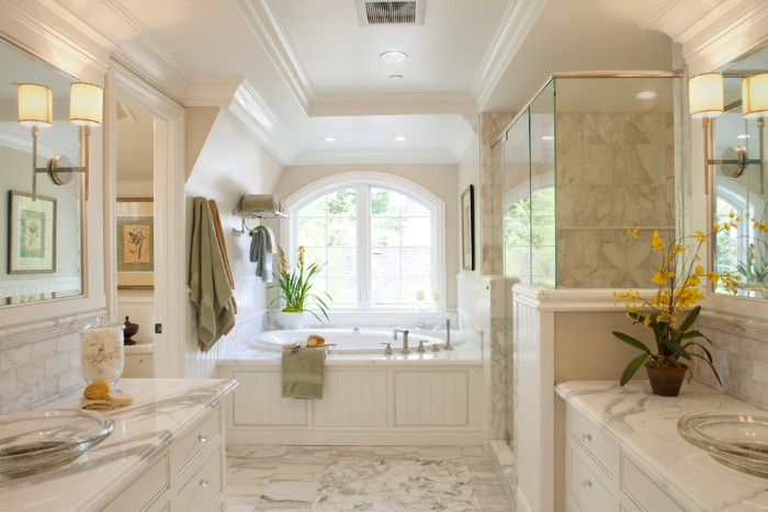 marble floor and wall tiles, inside a bright room, containing a round evevated tub, near a window, master bathroom remodel, two marble counter tops, with glass sinks