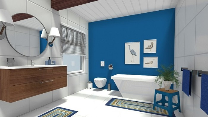 round mirror on a white paneled wall, inside a spacious room, with a cobalt blue bathroom accent wall, three framed images of birds, a bathtub and a small blue stool