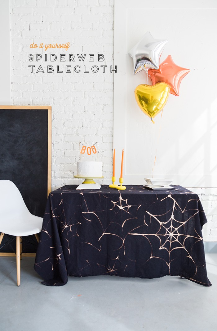 tablecloth in black, decorated with a pale, spider web pattern, made with bleach, halloween decorations, three balloons shaped like stars and a heart