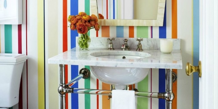 multicolored stripes on a wall, behind a marble sink, decorated with a candle, and a vase with orange flowers, best bathroom paint colors, mirror in an ivory-colored frame