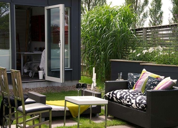coffee table in white, dark grey rattan couch, and a few chairs, in front of a modern she shed, with an open door