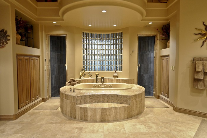 symmetrical room with an elevated bath at the center, two shower cabins, beige tiled floor, spa like bathrooms, wooden cupboards and decorations