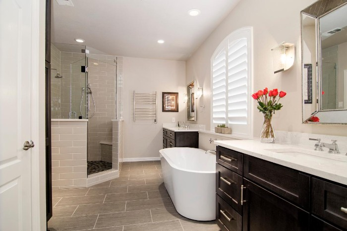 bouquet of red flowers, inside a vase, placed on a white counter top, near a sink, master bath remodel, oval white bathtub, beige tiles on the floor