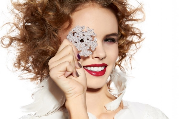 christmas makeup ideas, curly brunette woman, wearing red lipstick, and smokey eye makeup, smiling and holding a silver, glittering snowflake ornament, in front of one of her eyes