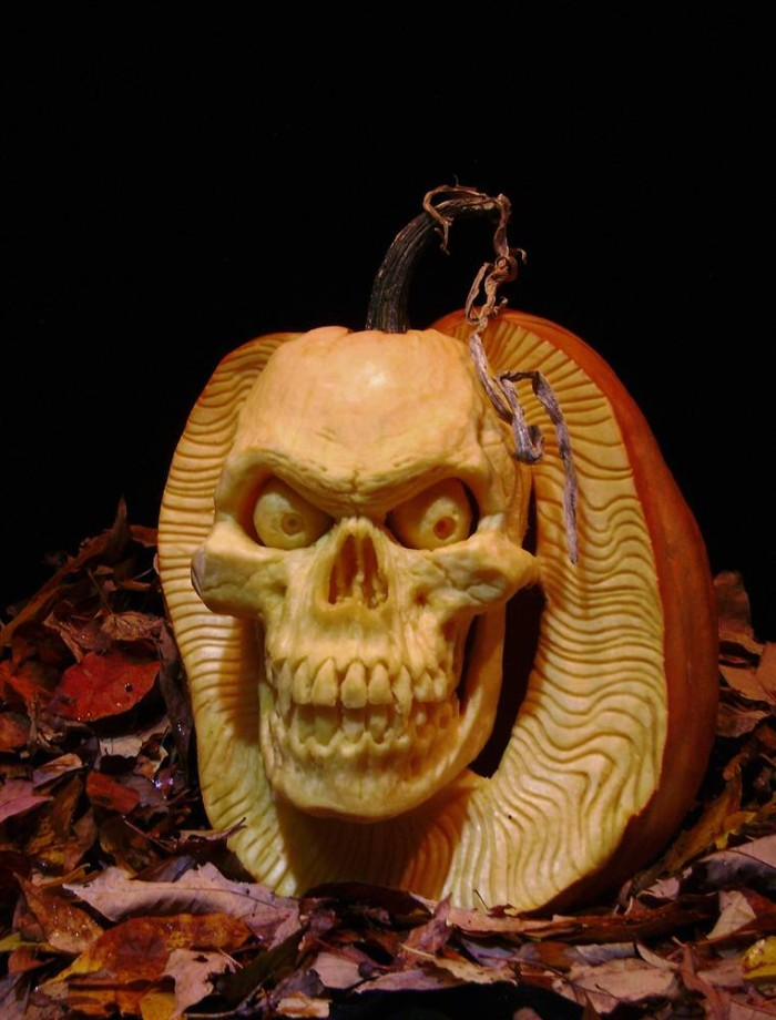 skeleton pumpkin, detailed and realistic carving, of an evil skull, made from an orange pumpkin, placed on a bed of red fall leaves
