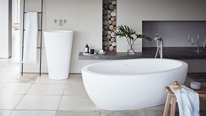 smooth oval bathtub, inside a room in pale cream and light grey, with a modern sink, and decorative wooden elements, master bathroom remodel