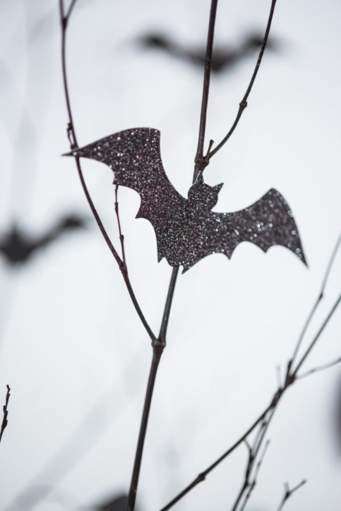 close up of a thin branch, decorated with a small, glittering bat shape, cut out from black card