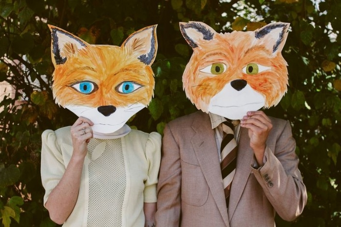 hand-painted paper masks, of fantastic mr. fox, and mrs fox, held in front of the faces of a man and a woman, quick halloween costumes, inspired by wes anderson
