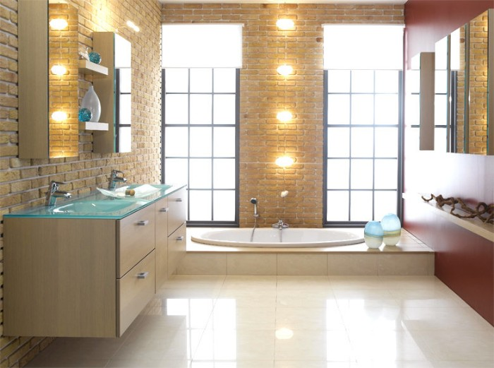 brick walls inside a bathroom, with smooth pale cream tiled floor, containing a bathtub, lamps and several cupboards