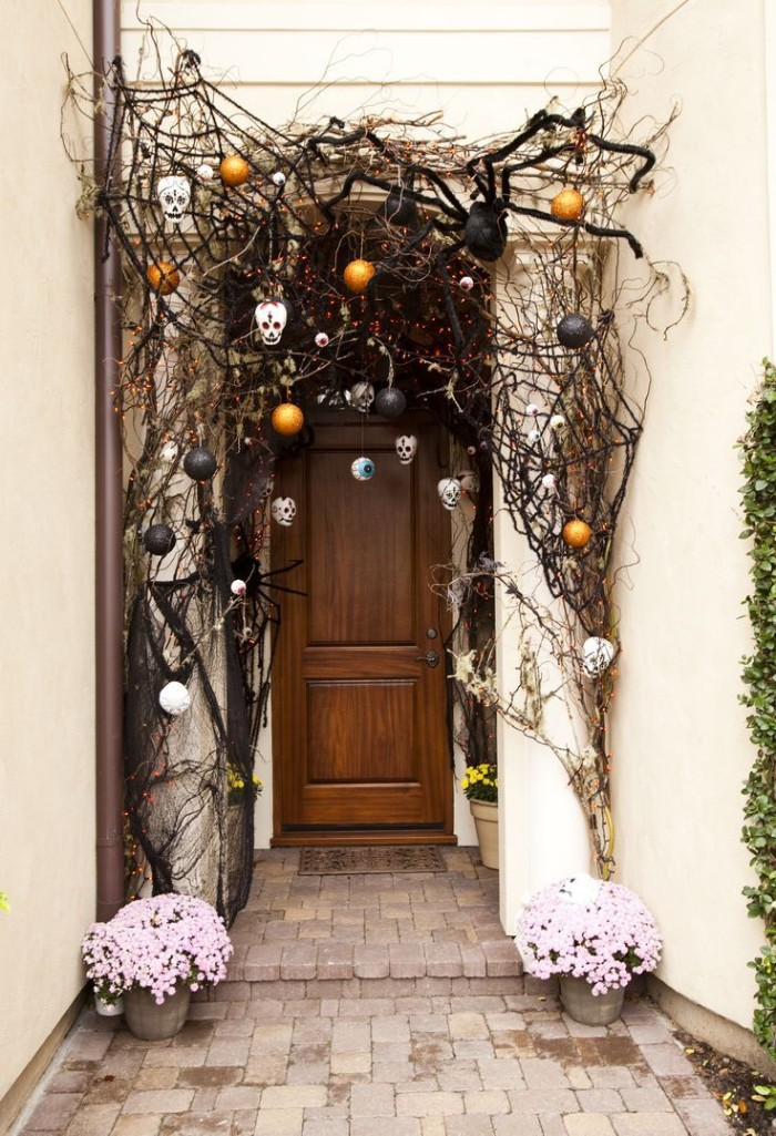 giant black spider ornament, black cobwebs and small white skulls, scary halloween decorations, near a front door, decorated with dried twigs, and black and orange baubles