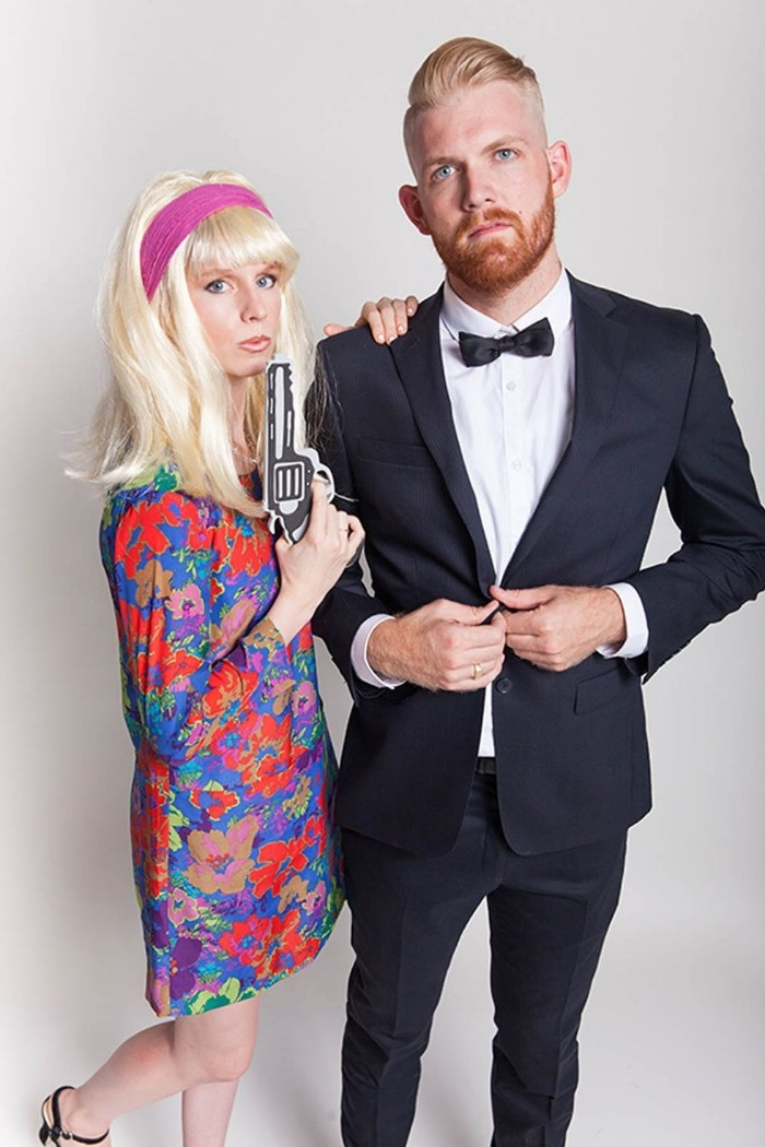 bearded man with blonde hair slicked back, dressed in a tuxedo, woman in a blonde wig, wearing a 1960s floral dress, and holding a faux gun, couple costume ideas, james bond and bond girl
