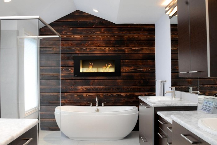 wooden bathroom accent wall, in dark brown, containing a small fireplace, in a white room, with a glass shower cabin, and a white bathtub