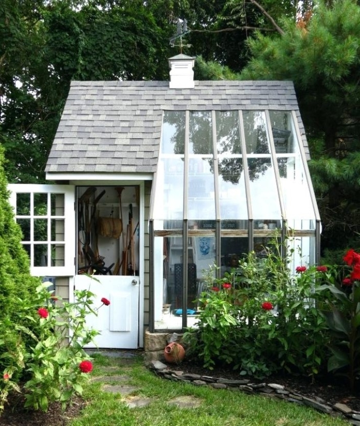 large glass panels, on an orangery style shed, with grey tiled roof, and a partially open door, revealing various tools inside