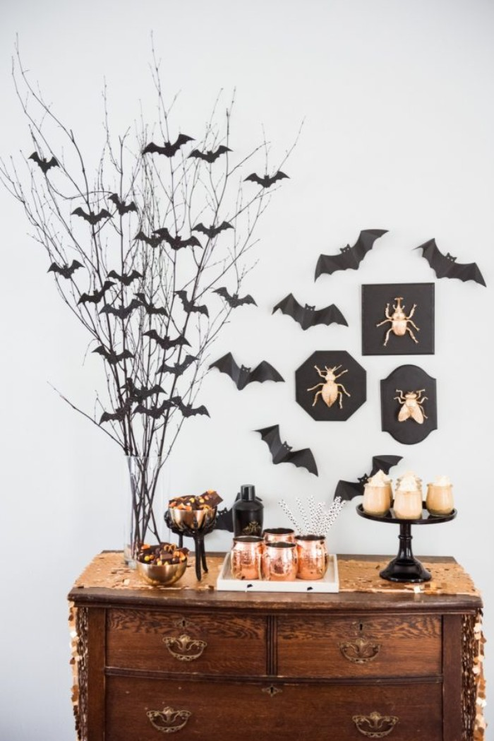 antique wooden cupboard, decorated with small dishes and candles, in black and gold, and a clear vase, containing dried branches, with small black bat shapes, insects ornaments and paper bats on the wall nearby