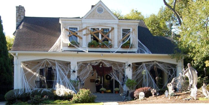 scary outdoor halloween decorations, house covered in fake cobwebs, with boarded windows, huge plastic spiders, and several skeletons in the yard