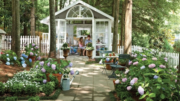 mother and young daughter, sitting in a shed, made of white wood and glass, in a garden with lots of flowers, she shed ideas, orangery style building