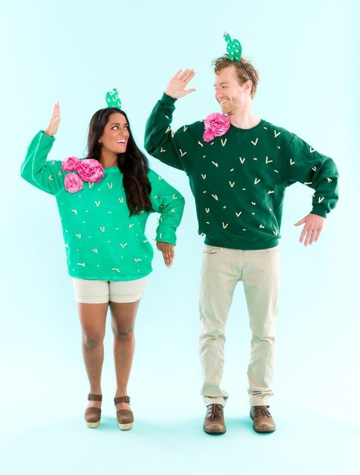 funny couple halloween costumes, smiling man and woman, dressed in green jumpers, decorated like cacti, small cactus hat, on both of their heads