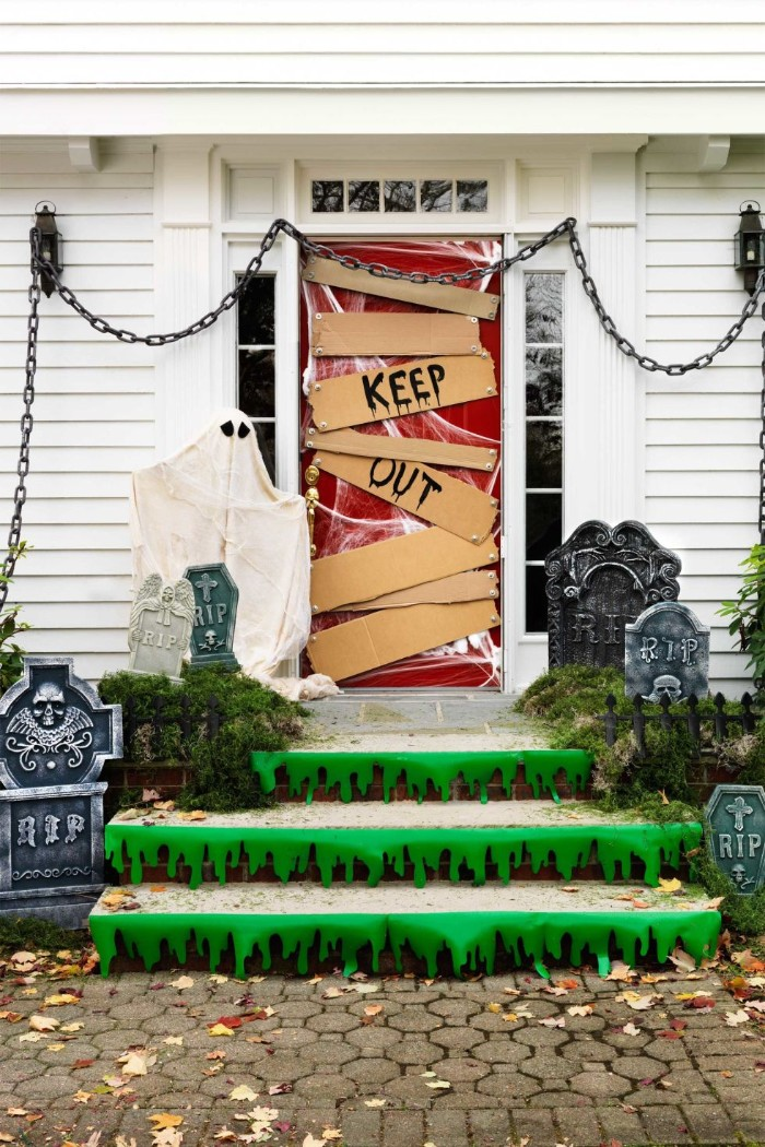red door boarded with pieces of cardboard, with the words keep out, written in black runny paint, scary outdoor halloween decorations, stairs covered with green stickers, looking like slime, chains and fake gravestones