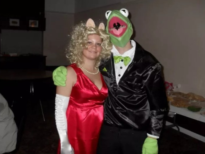 miss piggy and kermit the frog, dynamic duo ideas, inspired by the muppet show, woman in a red dress, with long white gloves, wearing a blonde curly wig, and pig ears, hugged by a man in a tuxedo, with a kermit mask