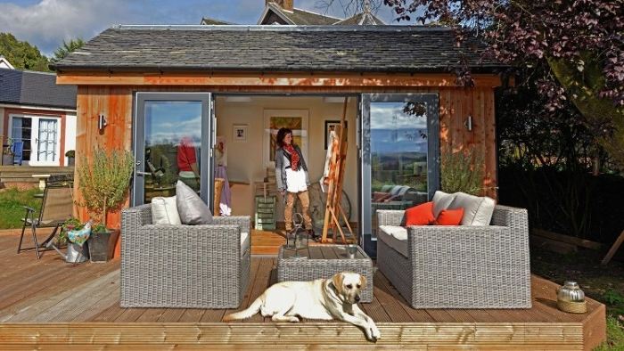rattan garden furniture, and a white dog, in front of a shed with open doors, woman standing next to an easel inside, she shed images