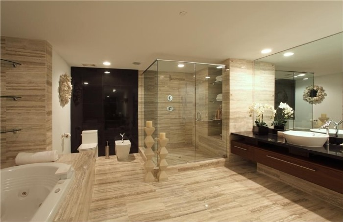 striped beige tiles, covering the floor and walls, of a large room, with a glass shower cabin, and an oval white tub, master bathroom remodel, large rectangular mirror
