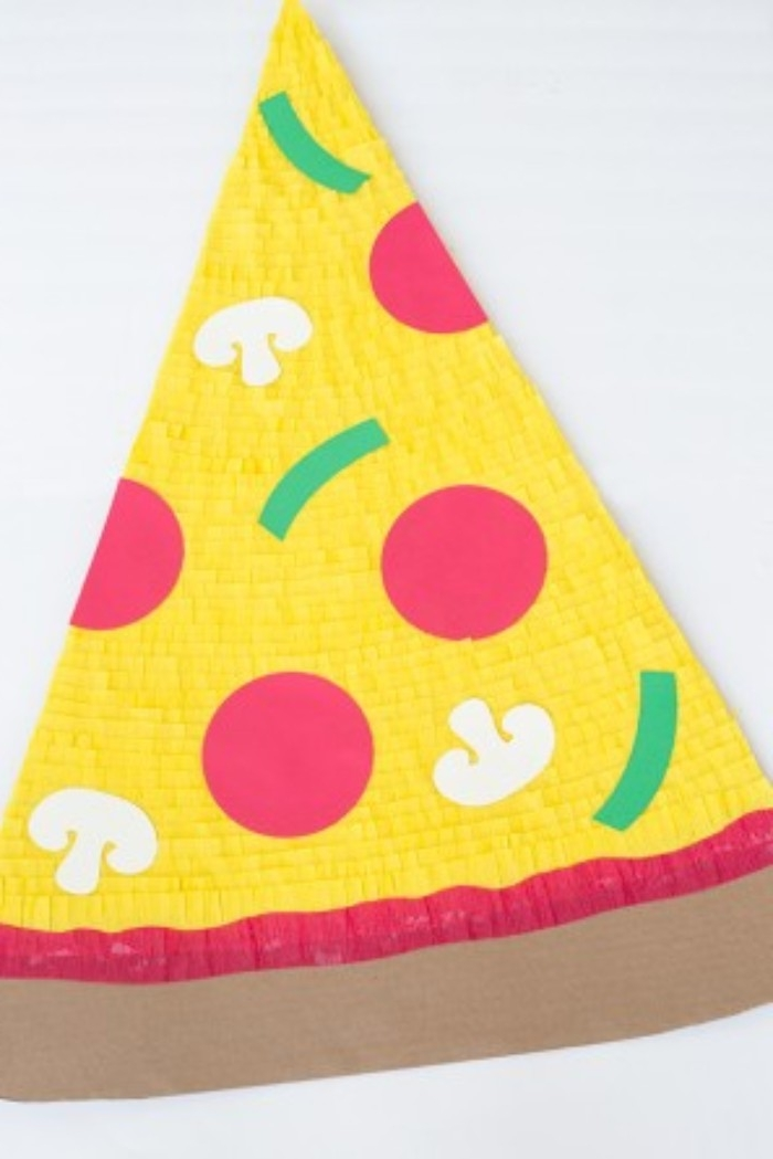 couples halloween costume ideas, giant piece of pizza, made from beige cardboard, covered in yellow tissue paper, and decorated with red, white and green cutouts