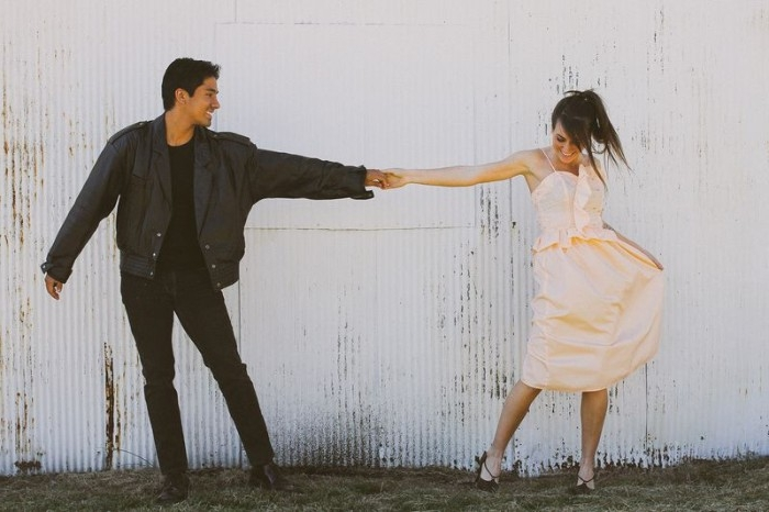 dancing smiling couple, young woman dressed in a pale peach dress, holding the hand of a man, with black clothes, and a black leather jacket, quick halloween costumes, inspired by grease
