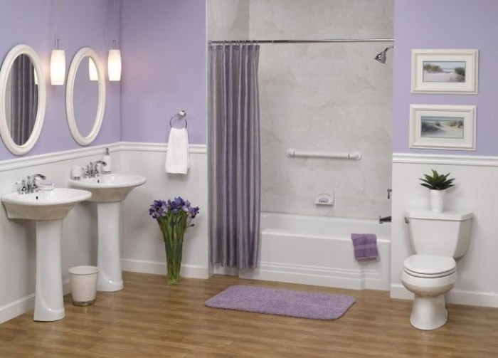 a set of identical white sinks, and two oval mirrors in white frames, in a room with pale lavender walls, and white wood paneling, bathtub and toilet