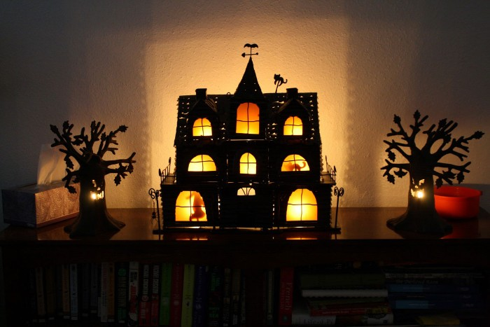 miniature haunted house decorations, a black house illuminated from within, and two small tree figurines with faces